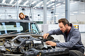 Male engineer repairing car with manager in background. Technologists is looking at motorvehicle in industry. Male and female professionals are representing teamwork in showroom.