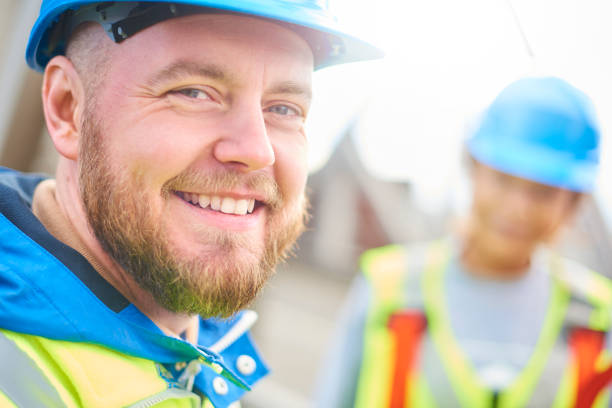 Male engineer smiles to camera male site engineer poses for the camera foreman stock pictures, royalty-free photos & images
