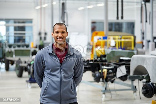 Portrait of engineer smiling in automobile industry. Confident male technologist is standing in showroom. He is wearing jacket in factory.