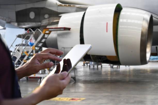 飛行機の力学のためのデジタルタブレットを使用して男性エンジニア - 航空整備士 ストックフォトと画像