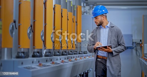Male engineer using digital tablet while examining manufacturing machinery in factory.