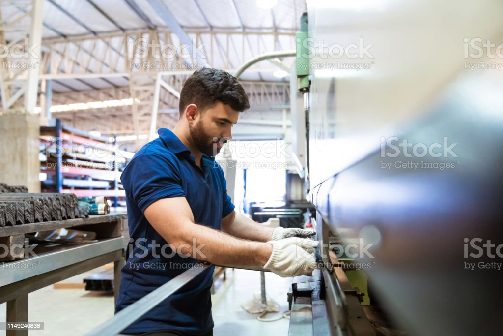 Male engineer using puller machine in factory Young male engineer using puller machine. Apprentice is working in manufacturing factory. He is wearing uniform. 20-24 Years Stock Photo