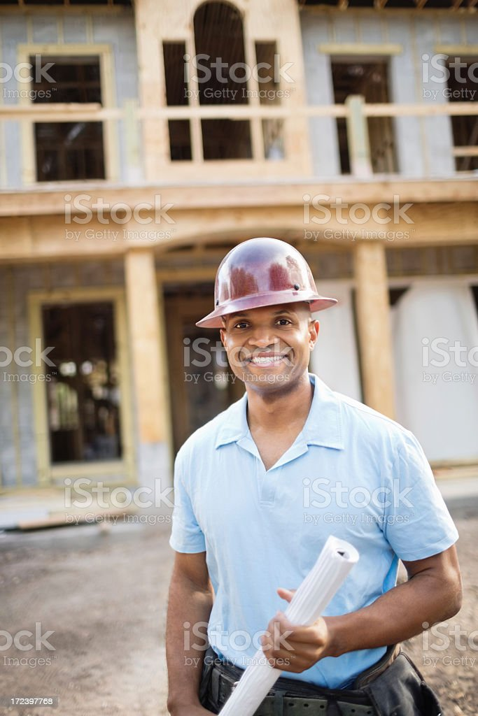 Male Engineer With Blueprint Standing In Front Of House royalty-free stock photo