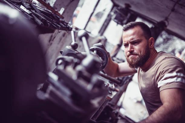 männliche ingenieur arbeiten an einem mechanischen bohrer auf hausgemachte workshop - hard to concentrate stock-fotos und bilder