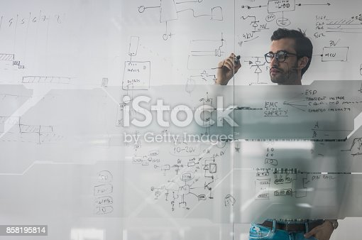 Young engineer drawing a diagram on a glass in the office. The view is through glass.