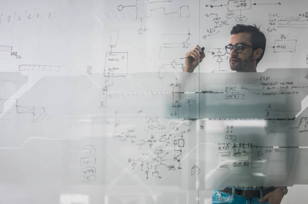 Male engineer working on new ideas and writing diagram on glass wall. stock photo