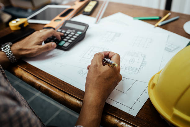 Male engineer working with house blueprint and analysis architectural plan on desk. stock photo