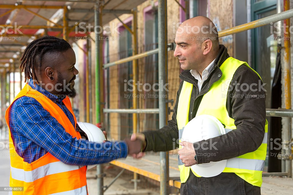 Male engineers with safety jackets and hardhats reaching an agreement stock photo