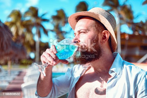 Male Enjoying Blue Cocktail In Vacation Resort