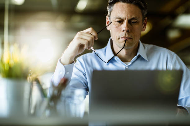Male entrepreneur reading an e-mail on laptop in the office. stock photo