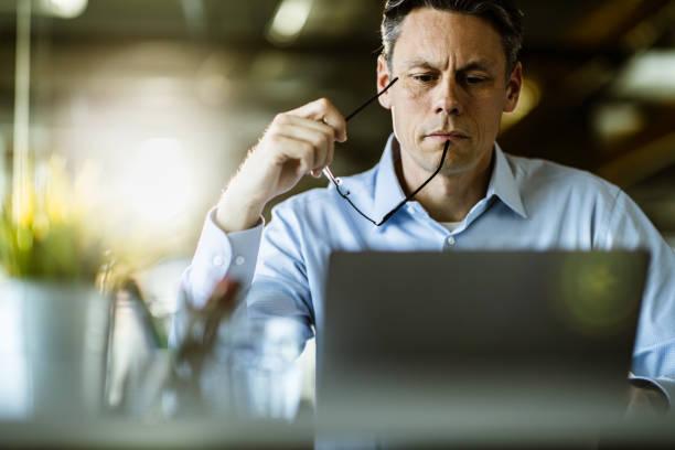 Männlicher Unternehmer liest eine E-Mail auf Laptop im Büro. – Foto