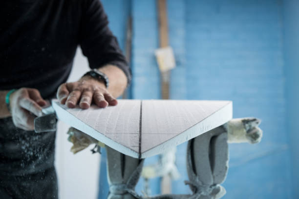 Male entrepreneur shaping the perfect surfboard for his client stock photo