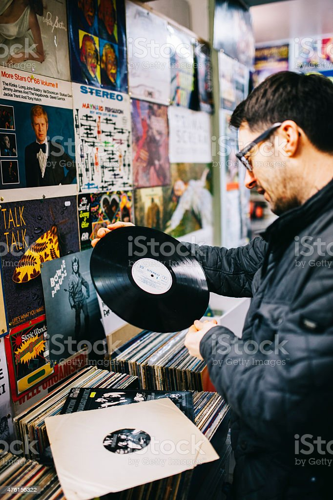 Male examining a second hand vinyl record, record store stock photo