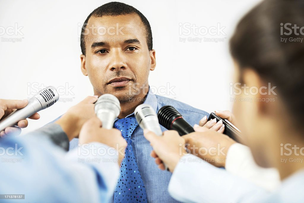 Male executive being questioned by journalists royalty-free stock photo