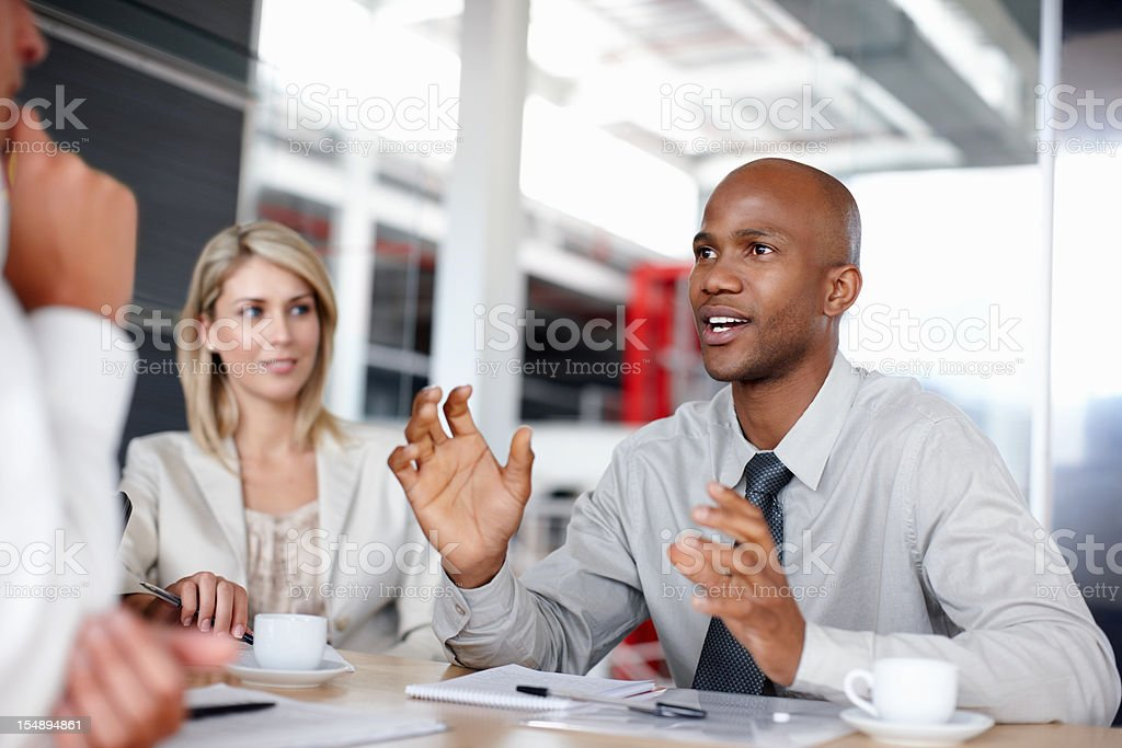 Male executive explaining business strategy to colleagues royalty-free stock photo