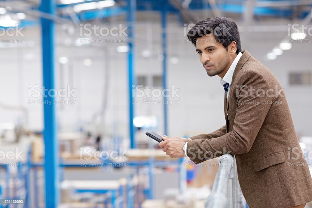 Male executive on factory balcony stock photo