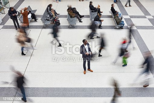 High angle view of 40 year old African businessman standing still in London transportation building while travelers walk by him in blurred motion.