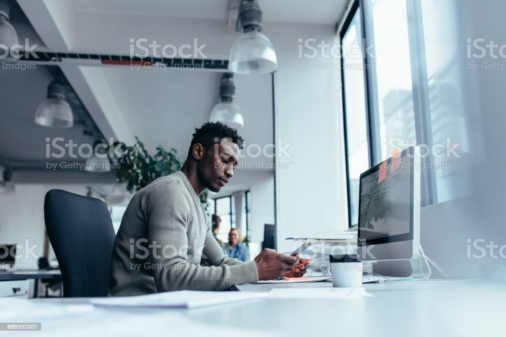 Male executive using mobile phone in office stock photo