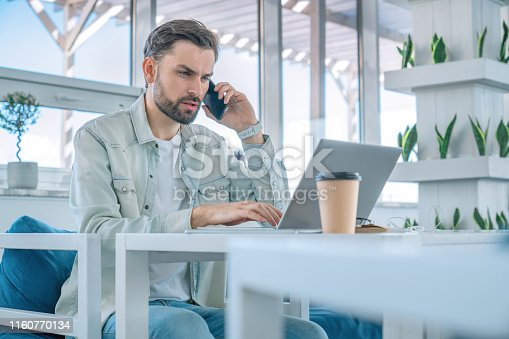 872006502 istock photo Male executive working in coworking space with phone and cup of coffee on table 1160770134