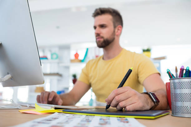 Male executive working over graphic tablet at her desk stock photo