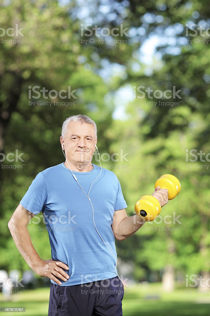 Male exercising with weight in a park stock photo