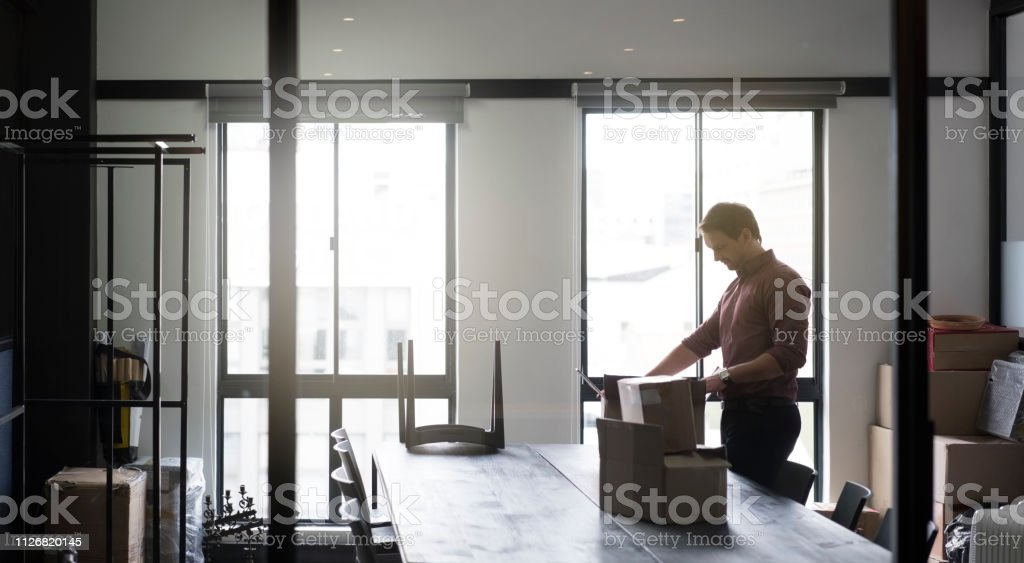 Male professional packing cardboard boxes at table. Businessman is...