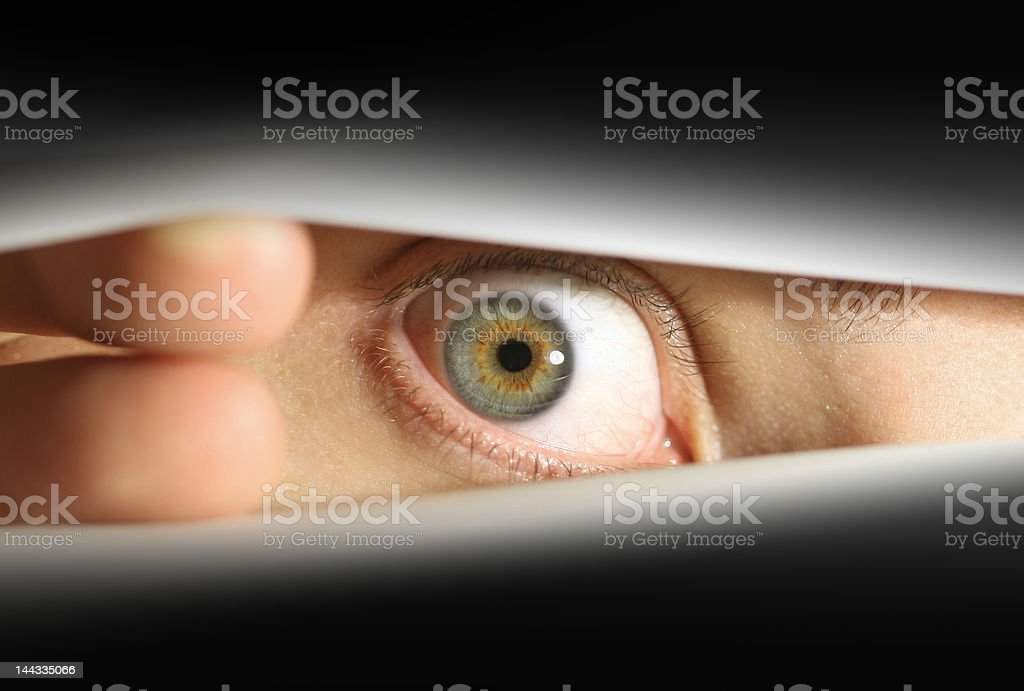 Male eye peering into envelope/package or through blinds stock photo