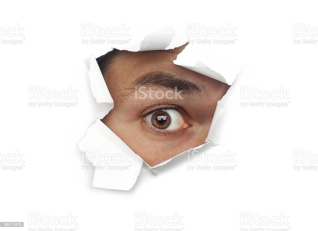 Male Eye Staring Out Through Ripped Paper Hole At Camera stock photo