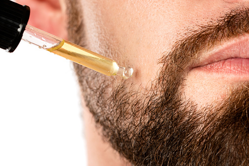 Closeup of male face and pipette with a oil for a beard growth