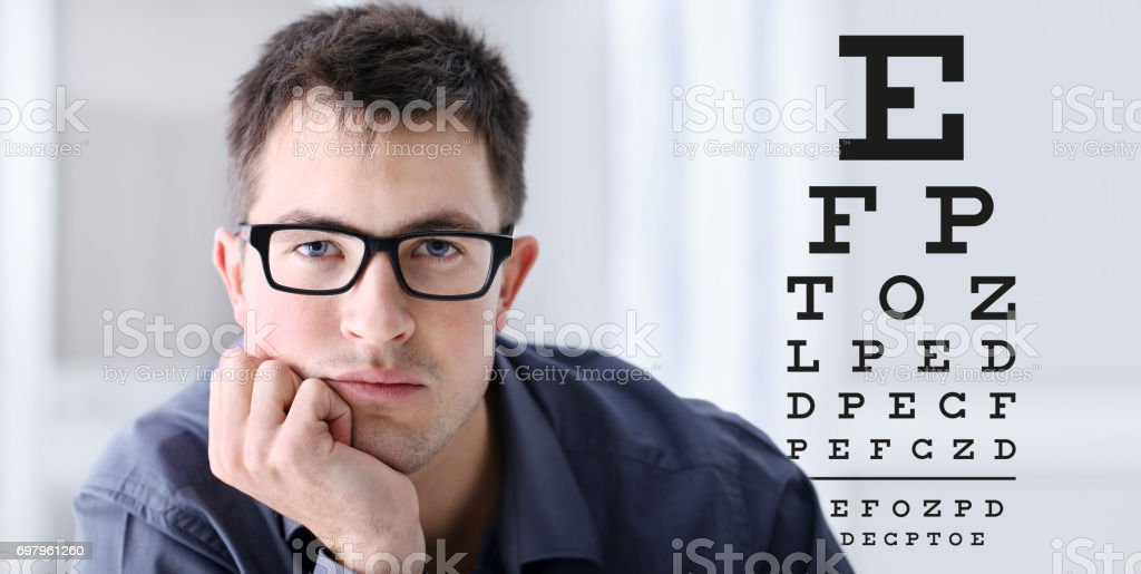 male face with spectacles on eyesight test chart background, eye examination ophthalmology concept stock photo