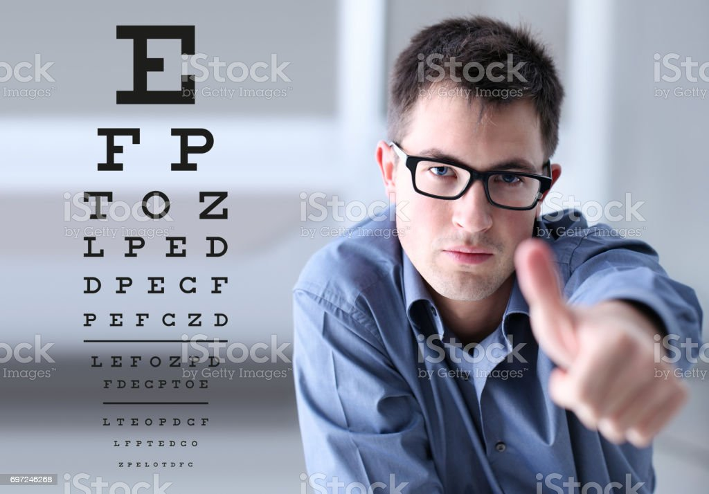 male face with spectacles on eyesight test chart background, showing...