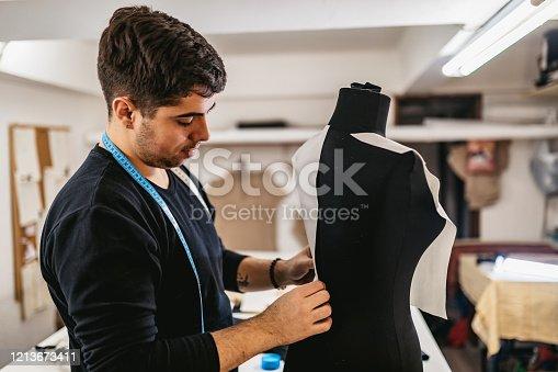 Young Caucasian male Fashion Designer In Studio Designing Mannequin.