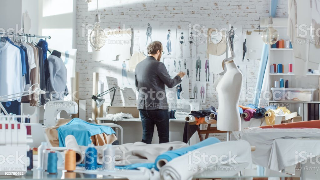 Male fashion, designer,  Pins Clothing Sketches to the Wall. His Studio is Sunny, Personal Computer Shows His Work. Colorful Fabrics, Clothes Hanging and Sewing Items are Visible. stock photo