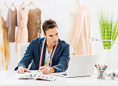 Young man fashion designer sketching and looking at laptop.