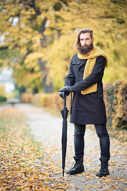 male fashion, fall colors, man with beard and umbrella - fall fashion stock photos and pictures