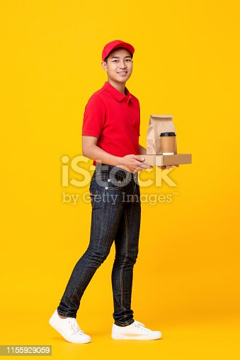 Young Asian male fast food crew in red uniform delivering take away meal in yellow isolated studio background
