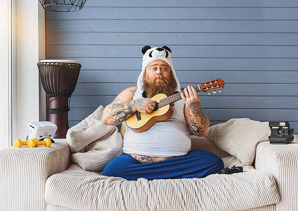 male fatso entertaining in his apartment - stomach sitting stock photos and pictures