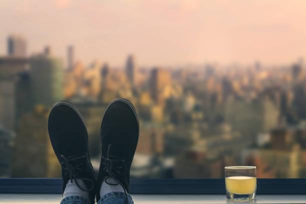 Eine männliche Füße in den Schuhen auf dem Balkon auf dem Hintergrund Manhattan. New York City – Foto