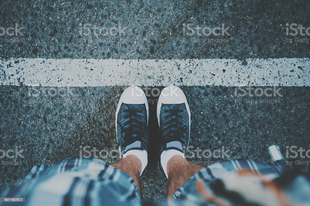 Male feet near white line on asphalt stock photo