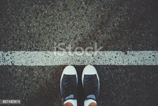 Male feet in white socks and gumshoes standing near grunge white line on gray asphalted road, ready to go