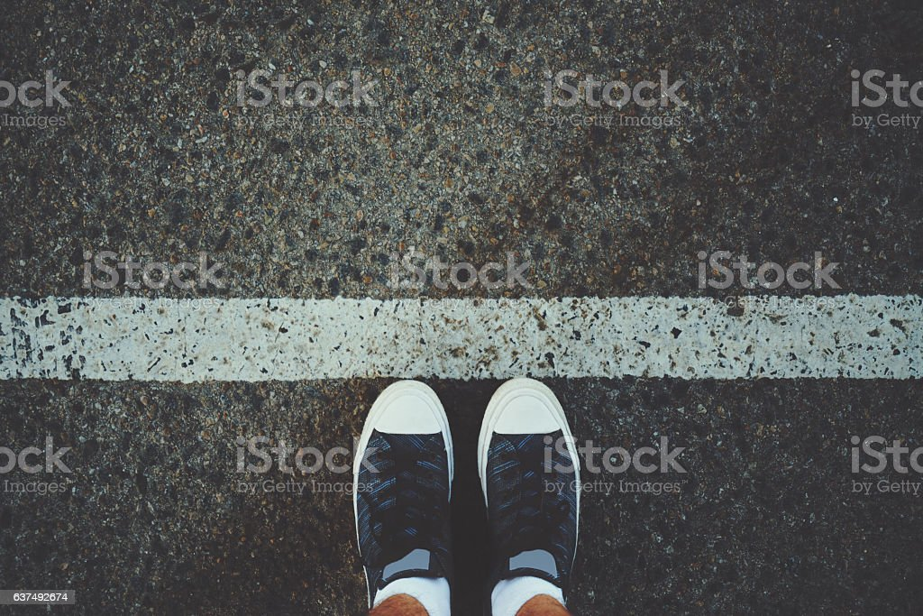 Male feet near white line on asphalt stock photo