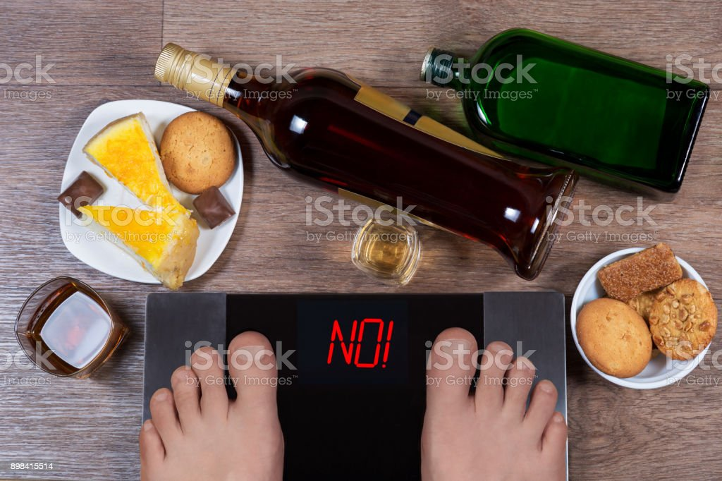 Male feet on digital scales with word no on screen. Bottles and glasses of alcohol, plates with sweet food. Concept of consequences of unhealthy lifestile. Morning after party. stock photo