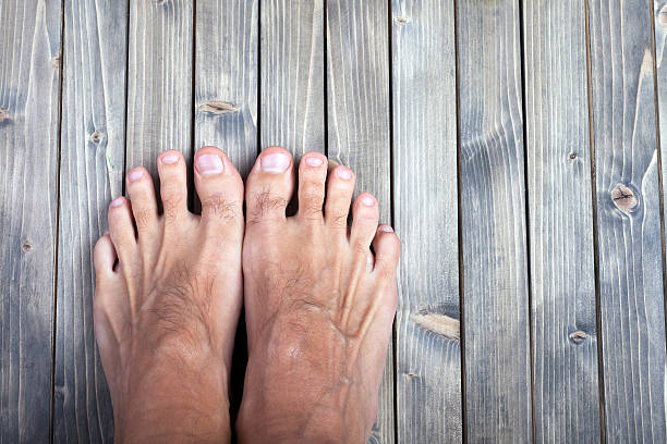 male feet on wooden background. male feet on wooden background male animal stock pictures, royalty-free photos & images
