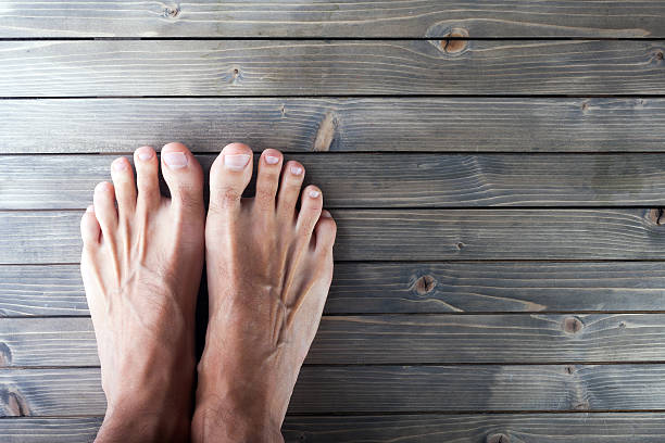 male feet on wooden background. - saubere zehen stock-fotos und bilder