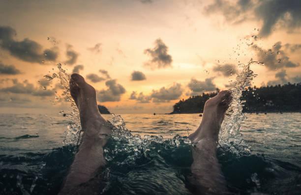 männliche Füße über die Wasseroberfläche mit Wasser sinkt während der goldenen warmen Sonnenuntergang im Ozean – Foto