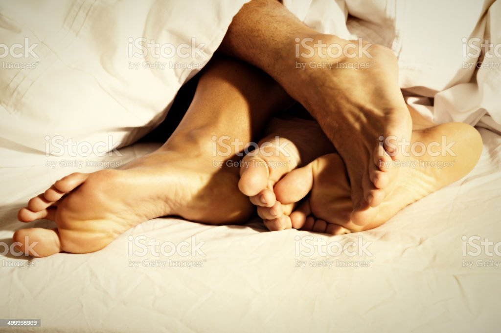 Male feet rub female feet in bed suggestively stock photo
