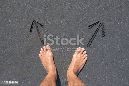 Man's feet standing in front of two arrows drawn on a black sand beach that are leading in two different ways