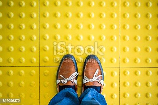 Male feet standing on blind pedestrian walking