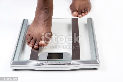 Male feet stepping on electronic scales for weight control on white background. The concept of slimming and weight loss