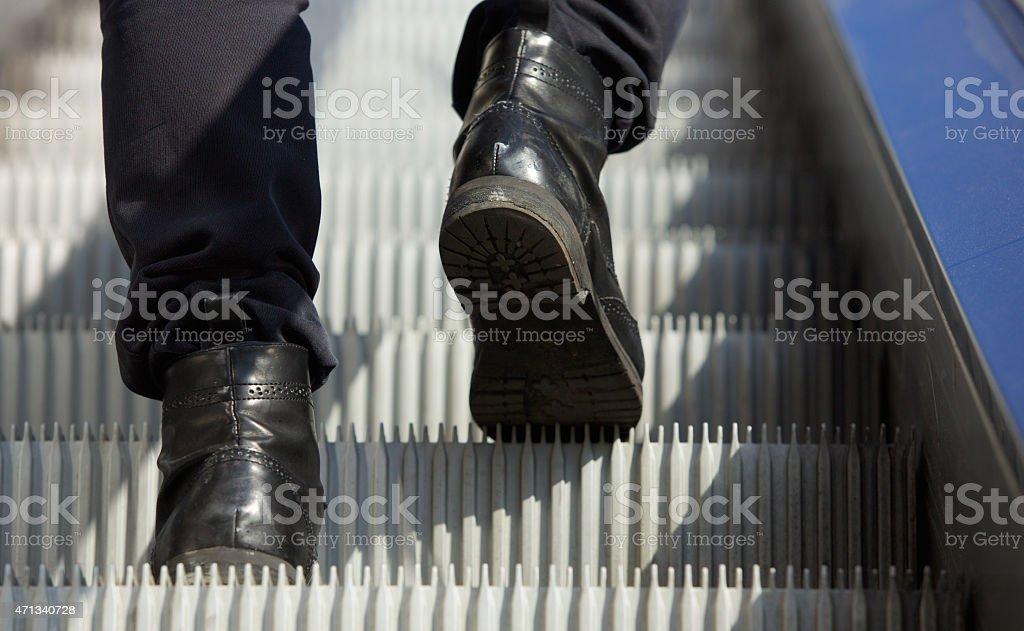 Male feet walking in boots up escalator stock photo
